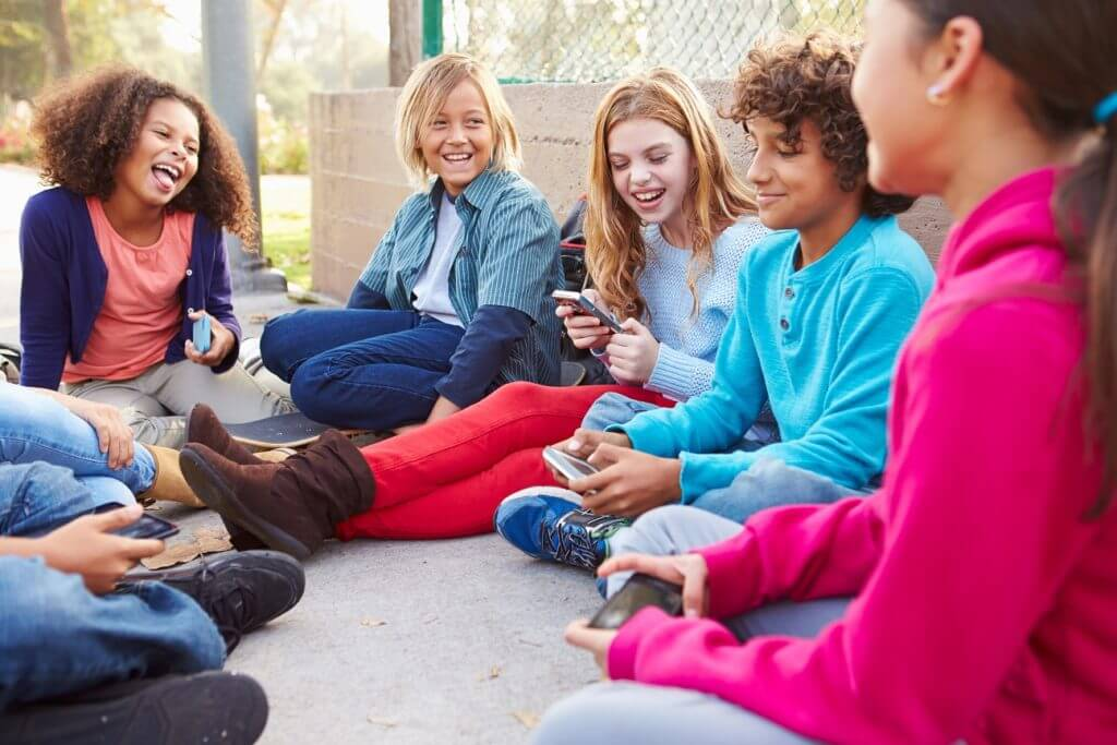 Group Of Young Children Hanging Out In Playground Smiling Using Mobile Phones