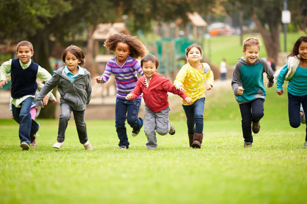 Group Of Young Children Running Towards Camera In Park Smiling